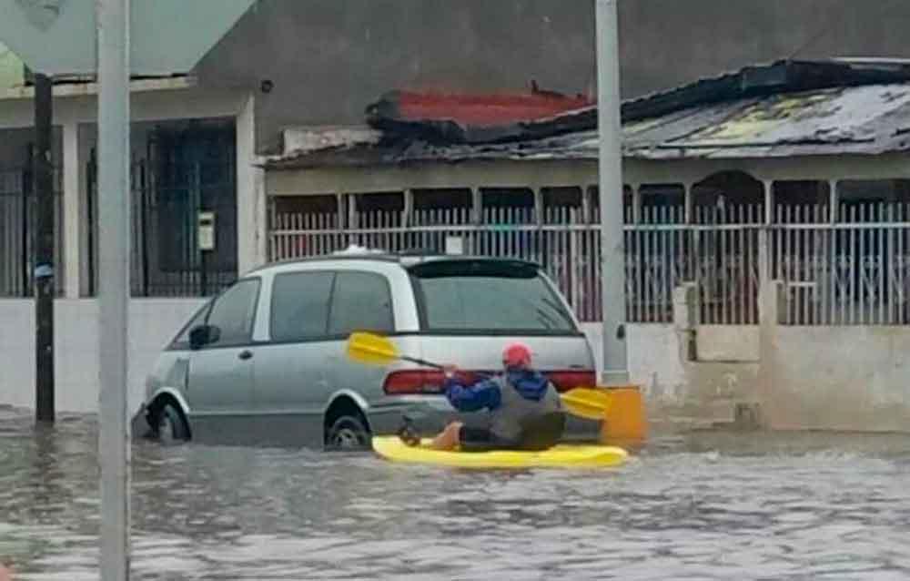 Hombre navega en kayak por las calles inundadas de Ensenada