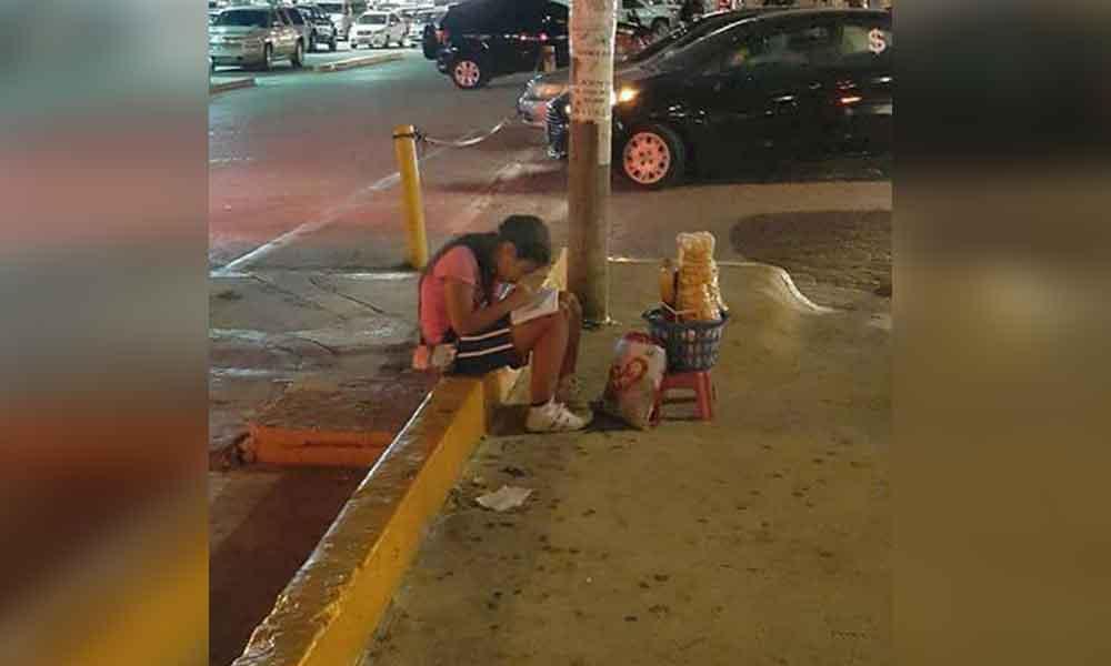 Gran lección de vida: una niña hace la tarea mientras vende dulces en la calle