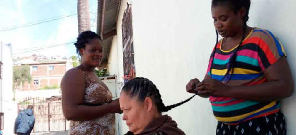 Mujeres haitianas hacen trenzas en Tijuana para ganarse la vida