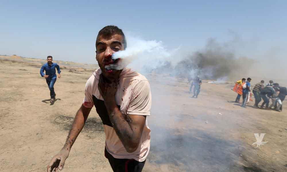 Soldado israelí dispara un bote de gas lacrimógeno al rostro de un manifestante durante una marcha en la frontera de Gaza