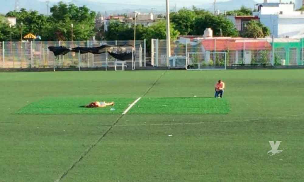 Encuentran a mujer asesinada en el centro de un campo de futbol