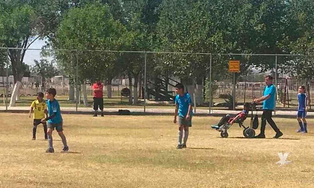 Papá empuja la silla de su hijo por todo el campo para que sienta lo que es jugar fútbol