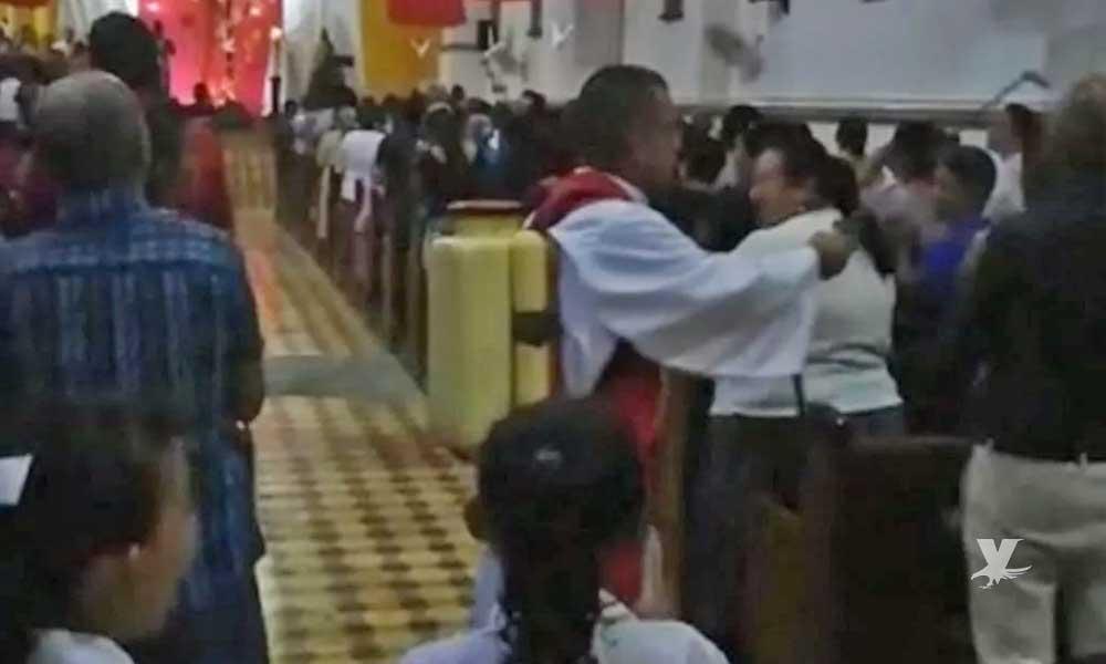 (VIDEO) Sacerdote es grabado utilizando un fumigador para rociar a los feligreses con agua bendita
