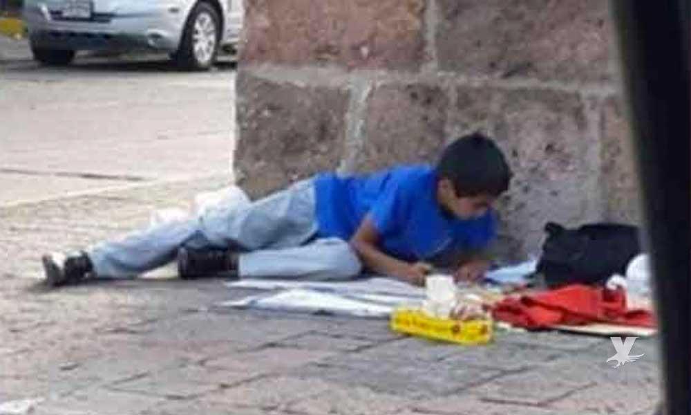(VIDEO) Niño vende dulces en la calle y en sus descansos realiza sus tareas escolares